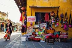Hoi An, Vietname - 2 de setembro de 2013: O turista está andando através da loja pequena na rua Imagens de Stock