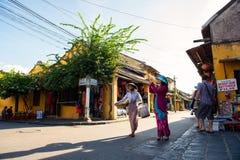 Hoi An, Vietname - 2 de setembro de 2013: O turista está tomando fotos na rua quando o vendedor andar transversalmente Foto de Stock Royalty Free