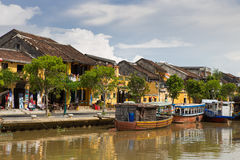 Hoi An. Wooden boats on the Thu Bon River in Hoi An Ancient Town Hoian, Vietnam. Yellow old houses on waterfront royalty free stock images