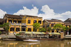 Hoi An. Wooden boats on the Thu Bon River in Hoi An Ancient Town Hoian, Vietnam. Yellow old houses on waterfront stock image