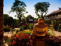 HOIAN,越南, 2017年9月, 04 :一budha的后面看法在一个古庙的有美丽的jarden与五颜六色 免版税库存图片