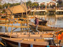 HOIAN,越南, 2017年9月, 04 :传统小船的未认出的人在古老建筑学前面在Hoi 库存图片