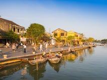 HOIAN,越南, 2017年9月, 04 :传统小船的未认出的人在古老建筑学前面在Hoi 免版税库存照片