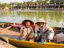 HOIAN,越南, 2017年9月, 04 :在传统小船的未认出的老夫妇在古老建筑学前面 库存图片