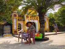 HOIAN,越南, 2017年9月, 04 :未认出的妇女坐在室外的一个ld房子在会安市古镇,联合国科教文组织 免版税库存图片