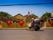 HOIAN,越南, 2017年9月, 04 :未认出的妇女骑自行车在与老房子的街道视图的和五颜六色的lanters 库存图片
