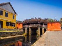 HOIAN,越南, 2017年9月, 04 :横渡在古老建筑学前面的未认出的人民传统小船  免版税库存图片