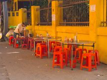 HOIAN,越南, 2017年9月, 04 :清洗桌的未认出的人在街道餐馆,与一些红色椅子 免版税库存图片