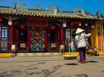 HOIAN,越南, 2017年9月, 04 :走和垂悬在他们的肩膀食物的未认出的妇女,在寺庙附近在 库存图片