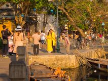 HOIAN,越南, 2017年9月, 04 :走近在古老建筑学前面的小船的未认出的人民在会安市 库存图片