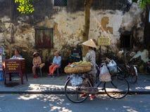 Hoian,越南- 2017年8月20日:走与自行车的未认出的妇女,在室外Hoi一个古镇,在越南 免版税库存图片