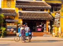 Hoian,越南- 2017年8月20日:走与自行车的未认出的妇女,在室外Hoi一个古镇,在越南 库存照片