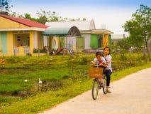 Hoian,越南- 2017年8月05日:骑自行车在路的未认出的孩子,回到家在会安市古镇,联合国科教文组织 免版税库存图片