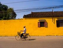Hoian,越南- 2017年8月05日:未认出的人骑自行车在一个老黄色房子前面的在会安市古镇,联合国科教文组织 免版税库存图片