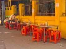 HOIAN, ΒΙΕΤΝΆΜ, 04 ΣΕΠΤΕΜΒΡΊΟΥ, 2017: Μη αναγνωρισμένο άτομο που καθαρίζει τους πίνακες σε ένα εστιατόριο οδών, με μερικές κόκκιν Στοκ εικόνες με δικαίωμα ελεύθερης χρήσης