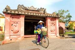 HOIAN, VIETNAM 23 GENNAIO: Donna di J che guida una bicicletta vicino al PAG giapponese immagine stock libera da diritti