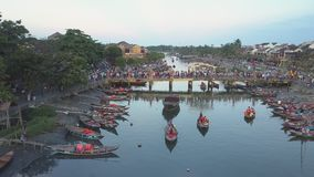Aerial pleasure boats sail on river against crowded bridge. HOIAN/VIETNAM - MAY 03 2018: Pictorial aerial panorama pleasure boats with tourists sail on river stock footage