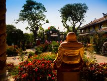 HOIAN, VIETNAM, SEPTEMBER, 04 2017: Back view of a budha in an ancient temple with a beautiful jarden with colorful Royalty Free Stock Image