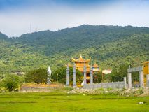 HOIAN, VIETNAM, SEPTEMBER, 04 2017: Beautiful view of an ancient temple in the horizont, with some green grass in the. Front, at hoian town in a sunny day in Royalty Free Stock Photography
