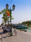 HOIAN VIETNAM, SEPTEMBER, 04 2017: Cyklar och motorcyklar som i rad in parkeras och ofrturist för några fartyg i vattnet Royaltyfri Bild