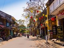 HOIAN VIETNAM, SEPTEMBER, 04 2017: Oidentifierat folk som går i gatasikten med gamla hus och färgrika lanters Fotografering för Bildbyråer