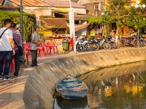 HOIAN, VIETNAM, SEPTEMBER, 04 2017: Unidentified man fishing in the border of the river whilse some people is walking. Near of him, in front of ancient stock images