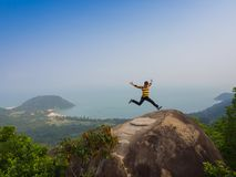 HOIAN, VIETNAM, SEPTEMBER, 04 2017: Unidentified man jumping over a huge rock with a beautiful view of the coastline of Royalty Free Stock Photo