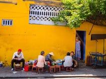 Hoian Wietnam, Sierpień, - 05, 2017: Niezidentyfikowani ludzie siedzi przy starym koloru żółtego domem w Hoi na zewnątrz antyczne Obrazy Stock