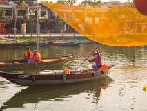 HOIAN, WIETNAM, WRZESIEŃ, 04 2017: Niezidentyfikowani ludzie w tradycyjnych łodziach przed antyczną architekturą w Hoi Zdjęcie Royalty Free