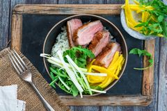 Hoisin duck with mango, spring onion, rocket lettuce salad and rice. Top view royalty free stock images