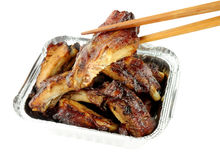 Hoisin Sauce Pork Ribs In Foil Take Away Tray. Hoisin sauce Chinese pork ribs in a foil take away tray isolated on a white background royalty free stock image