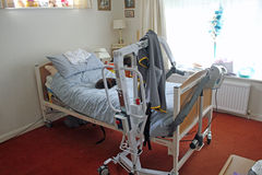 Hoist And Bed. This photo shows a hoist stored by a bed for a disabled person in a patients bedroom, this image can be used to highlight how a hoist might be Royalty Free Stock Photography