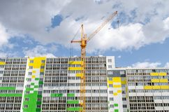 Hoist crane and multistory building. Construction of new building and hoisting crane Royalty Free Stock Photography