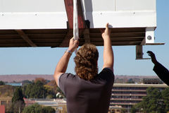 Hoist Support. Construction Worker leader a descending container Royalty Free Stock Photos