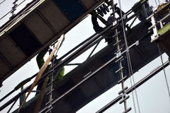 Hoist. Workmen on a hoist repairing windows in a tall building royalty free stock images