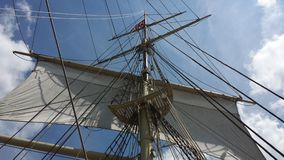 Hoisted main sails. Sails, mast, ropes and rigging on old-fashioned sailing ship with blue sky and clouds Royalty Free Stock Photo