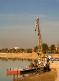Hoisting crane. A hoisting crane on a river Royalty Free Stock Image