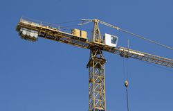Hoisting crane on a background of blue sky Stock Images