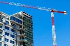 Hoisting crane and house Stock Photography