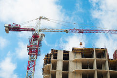 Hoisting crane and house construction. Construction of a skyscraper monolith and brick construction elements from a Royalty Free Stock Photography