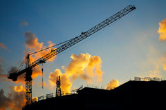 Hoisting crane silhouette on sunset sky stock image
