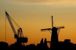 A hoisting crane and a windmill in sunset Stock Photos