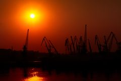 Hoisting cranes on sunset Royalty Free Stock Photo