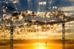 Hoisting cranes working on beautiful cloudy sky with golden sunset Stock Images