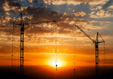 Hoisting cranes working on beautiful cloudy sky with orange sunset Royalty Free Stock Photography