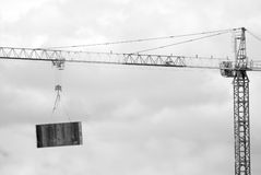 Hoisting tower crane elevates construction panel Stock Images