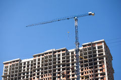 Hoisting tower crane and top of construction building Stock Images