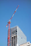 Hoisting tower crane on top of construction skyscraper building over blue sky Stock Photography
