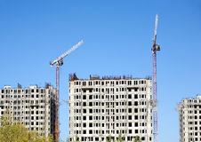 Hoisting tower cranes and top of construction buildings Royalty Free Stock Images