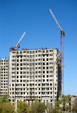 Hoisting tower cranes and top of construction buildings Stock Images